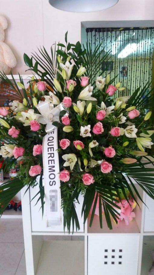 Centro de flores para funeral con rosas rosas y lilium