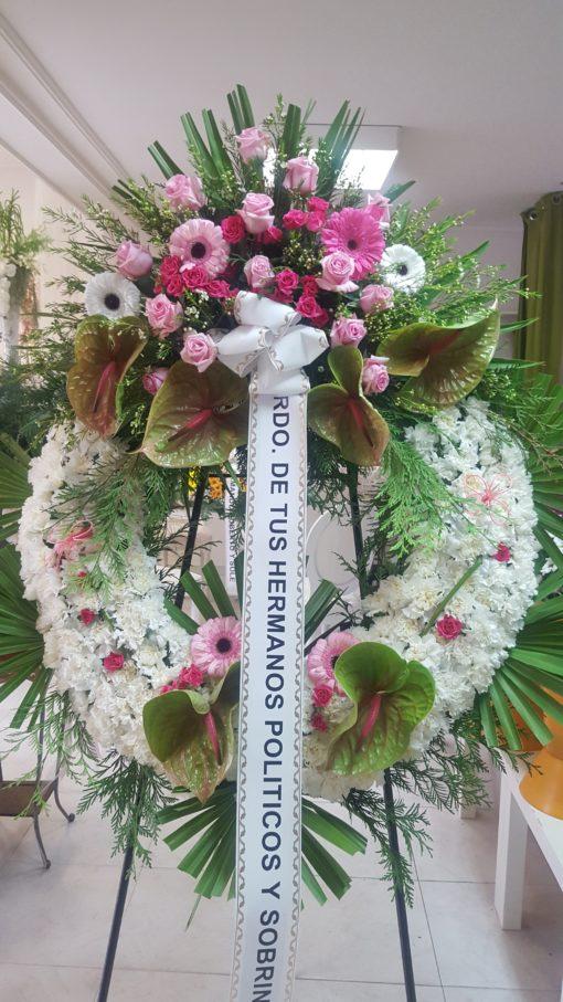 Corona con claveles blancos y centro de gerberas, rosas